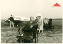 Schwarz-Weiß-Bild: Ein mittelalter Mann im Rollstuhl der 60er Jahre, im Hintergrund Damen und ein weiterer Rollstuhl sowie ein Sportflugzeug, vor dem ein Mann mit dem Rücken zum Betrachter steht
